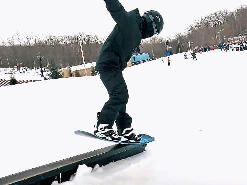 snowboarder doing nose press in the park